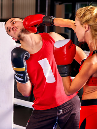 Female boxer throwing right cross at mitts with her trainer in ring. Boxing training in sport gym. Stock Photo