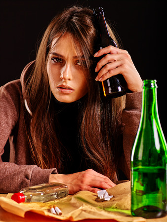 drinking alcohol: Girl in depression drinking alcohol and smokes cigarettes in solitude. Drinking habits. Girl is heavy drinkers on black background.