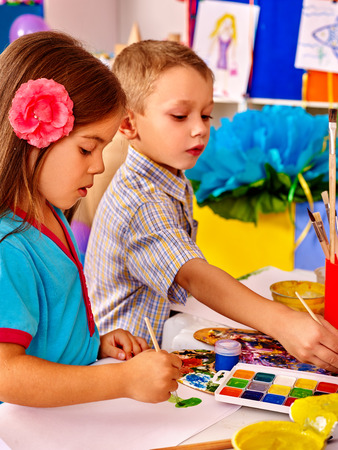 Two children girl and boy with brush painting on table in primary school. Painting children lesson in primary school. Stock Photo