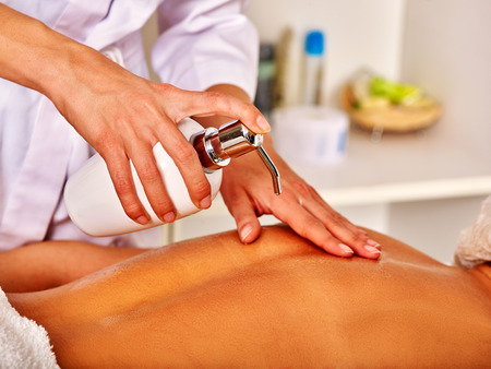 Body part of woman middle-aged take back massage in spa salon with young beautician. Massage concept.