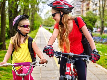 bike lane: Girls wearing bicycle helmet and glass with rucksack ciclyng bicycle. Girls children cycling on yellow bike lane.