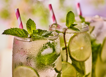 country life: Alcohol drink. On wooden boards three high glasses with alcohol drink and ice cubes. Drink number two hundred ninety-five cocktail mohito with mint leaf sprig . Country life. Light background. Stock Photo