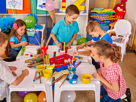 children painting: Children without teacher painting on paper at table in primary school. Children learn on their own by paint colors. Stock Photo