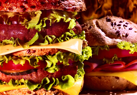 double oven: Wooden board double patty hamburger on background of fire. Group of hamburger close up. Hamburger with cheese.