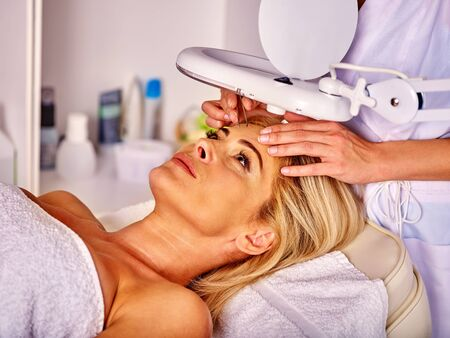 tweezing: Woman middle-aged in spa salon with young beautician. Tweezing eyebrow by beautician. Woman beauty and healthy. Stock Photo