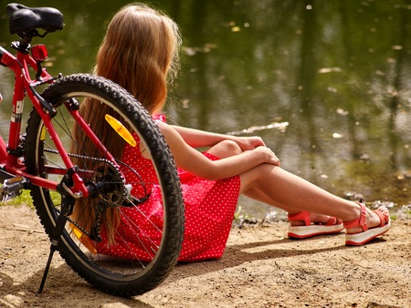 lunares rojos: Girl with bicycle. Girl wearing red polka dots dress rides bicycle into park. Girl sits on bicycle on shore river. Sun day. Foto de archivo