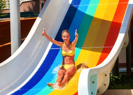 slide show: Nice beautiful girl on water slide at water park show thumb up. Water slides with flowing water in water park. Summer water park holiday. Outdoor in hot summer.
