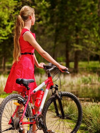 lunares rojos: Bicicletas bicicleta chica. Ni�as el uso de lunares rojos vestir paseos en bicicleta en el parque tiene descanso. Chica en el ecoturismo. El ciclismo es bueno para la salud. Ciclista mirar hacia otro lado. Vista trasera.