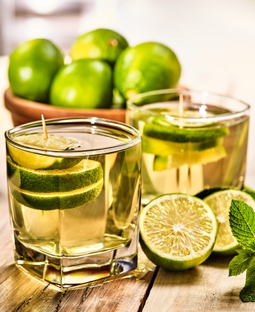 quencher: Country drink. On wooden boards is glass with green transparent drink and lime glue bowl. Drink number one hundred eighty five mojito with mint leaf . Country life. Wooden boards background.