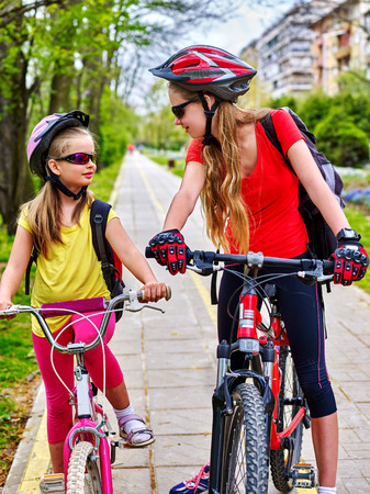 bike lane: Bikes bicyclist girl. Girls wearing bicycle helmet and glass with rucksack ciclyng bicycle. Girls children cycling on yellow bike lane. Bicycle girl talk each other.