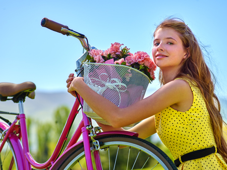 Teenager girl wearing yellow polka dots dress looking dreamily keeps bicycle with flowers basket. Lot of green tree and blu sky in park. Romantic style. Girl grabbed basket of flowers on bicycle . Stock Photo