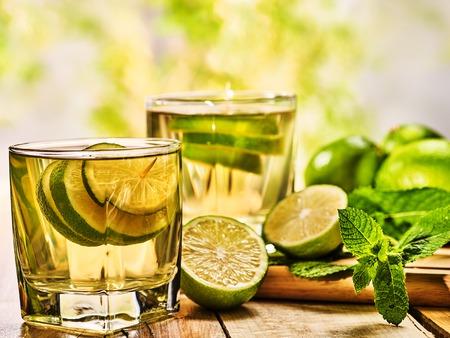 стиль жизни: Алкогольный напиток. Деревянные доски два бокала с алкоголем зеленый прозрачный напиток. Пить номер двести восемьдесят один мохито коктейль с половиной лайма и мяты. Зеленый свет фон. Фото со стока