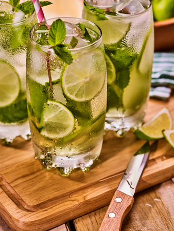 top seven: Alcohol cocktail. On wooden boards three glasses with alcohol drink and ice cubes. Drink number two hundred eighty seven cocktail mohito with knife and mint leaf. Country still life. Top view. Stock Photo