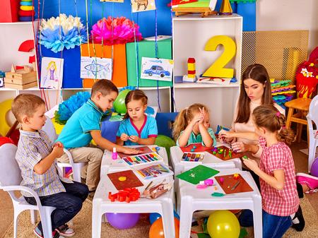 Skupina chytrých dětí s mladou krásnou učitelskou formou z plastelínu na základní škole. Dětské školní vzdělávání.
