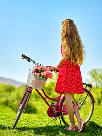 lunares rojos: Bikes bicycle girl. Slim beautiful girl wearing red polka dots dress looking into distance keeps bicycle with flowers basket. Green grass. Back view of girl on bicycle wearing sundress .