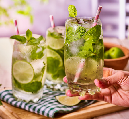 country life: On wooden boards three glasses with alcohol drink and ice cubes. Drink three hundred and eleven cocktail mohito with female hand and lime and mint leaf. Country life. Outdoor. Light background.