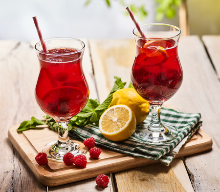 On wooden boards are ice cold beverage two glasses with red berries lemon cocktail . Alcohol country cocktail beverage number three hundred and sixteen with leaf mint. Outdoor cocktail . Sun morning. Stock Photo