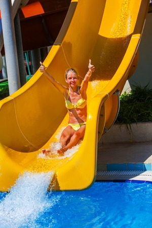 slide show: Happy child on yellow water slide and bikini at water show thumb up. Water slides with flowing water and splash in blue water park. Stock Photo