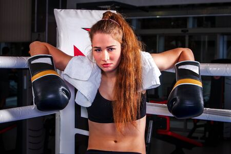 Sport strong boxing girl wearing black boxing gloves sitting in corner of boxing ring and have rest.