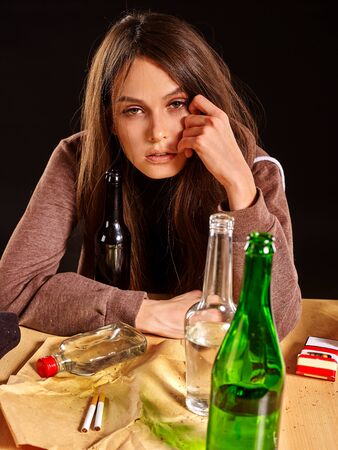 dipsomania: Drinking girl in heavy depression drinking alcohol and smokes cigarettes in solitude. Drinking habits. Girl is heavy drinkers. Girl head prop hand and looks in camera on black background. Stock Photo
