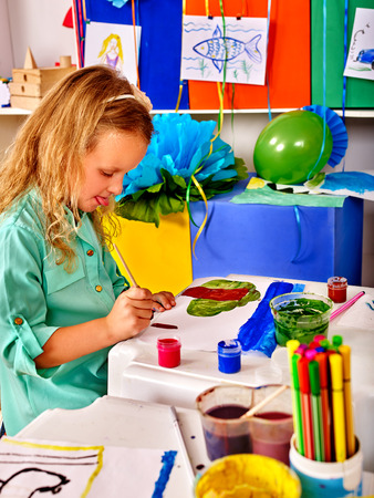 kindergarden: Close up of little child girl painting picture on desk in primary school. In primary school lot of child picture in kindergarden. Stock Photo