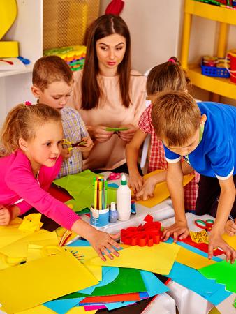 Gran grupo de niños con el maestro cómoda que hace algo fuera de papel de colores sobre la mesa en la escuela primaria. lección, los niños de artesanía en la escuela primaria. Childrens artesanías de papel.