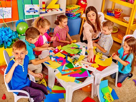 Gran grupo de niños con el maestro están haciendo algo fuera de papel de colores sobre la mesa en la escuela primaria. Childrens artesanías de papel. Vista superior de la escuela primaria.