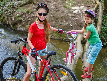 eldest: Two girl rides bicycle. Two girl cycling fording throught water . Cycling trip is good for health. Cyclist watch your step. Eldest bicycle girl helping bicycle younger girl.