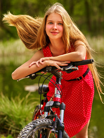 blond girl: Bicycle girl. Girl wearing sundress rides bicycle into park. Girl in ecotourism. Bicycle is good for health. Bicycle girl have long blond hair.Long hair of bicycle girl fluttering in wind. Stock Photo