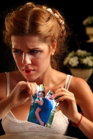 photo pictures: Unhappy girl in wedding dress tearing wedding pictures. Wedding depression. Model on photo is the same image in the picture.