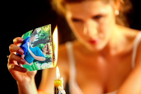 tearing: Uhappy girl burn love photos. Love is gone. Model on photo is the same image in the picture.