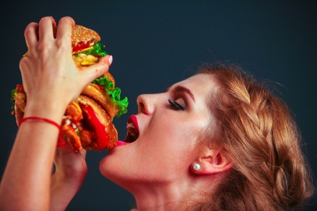Girl with mouth wide open hamburger eating hamburger. Hamburger is tasty food.