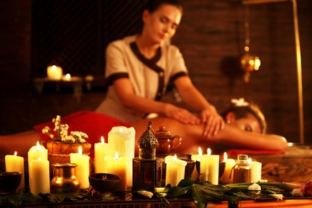 masseuse: Young woman lying on wooden spa bed. Massage in spa salon with masseuse . Girl on candles background in massage spa salon. Stock Photo