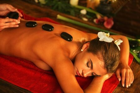 lastone: Young woman lying on wooden spa bed. Lastone therapy massage in spa salon. Girl on candles background in massage spa salon. Stock Photo