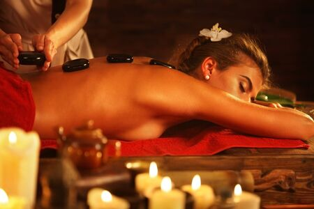 lastone: Woman lying on wooden spa bed. Lastone therapy massage in spa salon. Girl on burning candles background in massage spa salon.