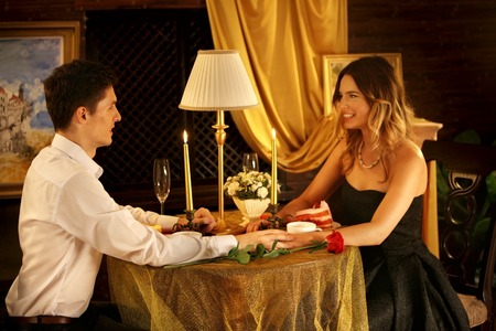 red dress: Loving couple dinner in restaurant. Couple talk to each other. Man gently touch hands girlfriend. Stock Photo