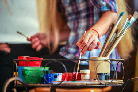 Middelste deel van meisje kunstenaar schildert portret van vrouw met potlood. Meisje schilder van achteren gezien. Het meisje schildert door potlood op ezel. Penselen en de voorgrond. Stockfoto