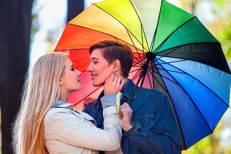 pareja abrazada: joven pareja feliz abrazando bajo el paraguas en día de otoño. Muchacha que va a besar a su amante.