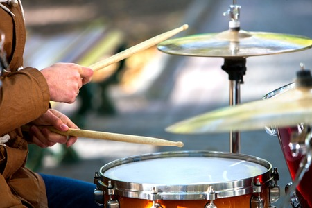 improvisation: Music street performers on autumn outdoor. Middle section of body part. Visible hands with drumsticks Stock Photo