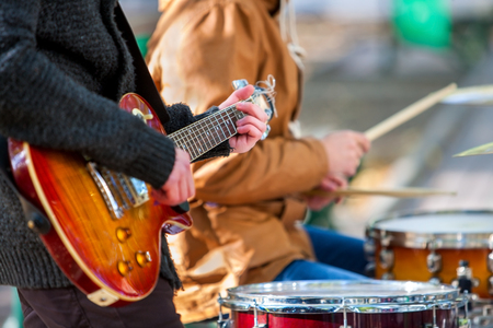 Music street performers on autumn outdoor. Middle section of body part with guitar.