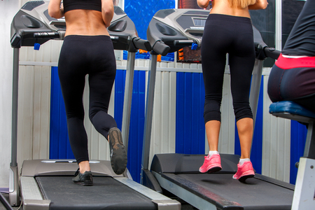 cardio workout: Middle section of running woman on treadmil at gym. Cardio workout of group girls.