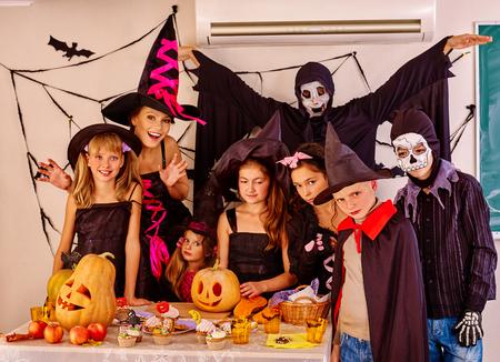 treats: Fiesta de Halloween con los niños del grupo que llevan a cabo el truco o tratar de Halloween en interior.Two adulta en traje de Halloween.