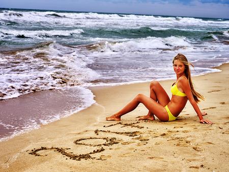 sand writing: Summer girl sea. Girl sitting on beach of sea. Girl in swimsuit is writing on sand numeral 2017 near sea with waves. Stock Photo