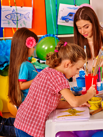 children painting: Children with teacher woman painting on paper at table in kindergarten .Children working together.