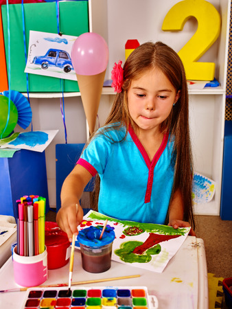 kindergartener: Portrait of little girl with brush painting on table in kindergarten . Girl learns to paint. Independent work. Stock Photo