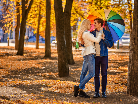 love kissing: Young couple kissing in yellow autumn park . Loving couple kissing in sun in autumn park. Yellow foliage in autumn park. Stock Photo
