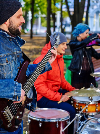 improvisation: Group of music street performers with girl violinist on autumn outdoor. Music people play drums.