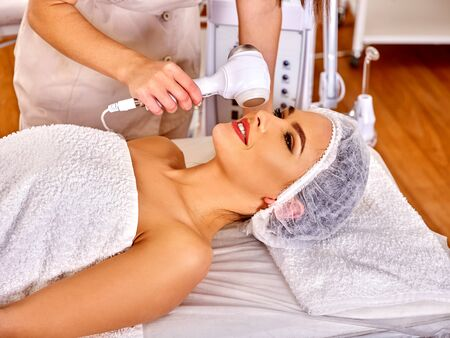 depressor: Young woman receiving electric facial massage on microdermabrasion equipment at beauty salon. Healthy lifstyle.