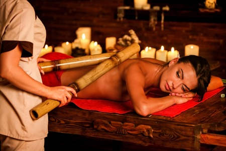 Bamboo back massage. Young woman lying on wooden spa bed have bamboo massage therapy sticks. Bamboo massage in spa salon. Girl on candles background in massage spa salon. Stock Photo