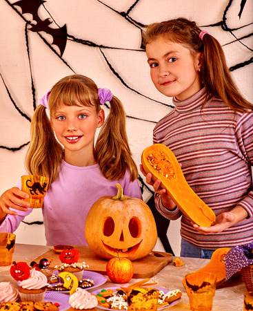 children party: Halloween party with children two girls making carved pumpkin. Halloween children table.
